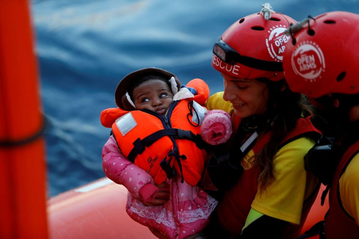 A crew member of MV Open Arms, the search-and-rescue ship of Proactiva Open Arms, carries a migrant baby before passing it to crew members of MV Aquarius, a search-and-rescue ship run in partnership between SOS Mediterranee and Medecins Sans Frontier