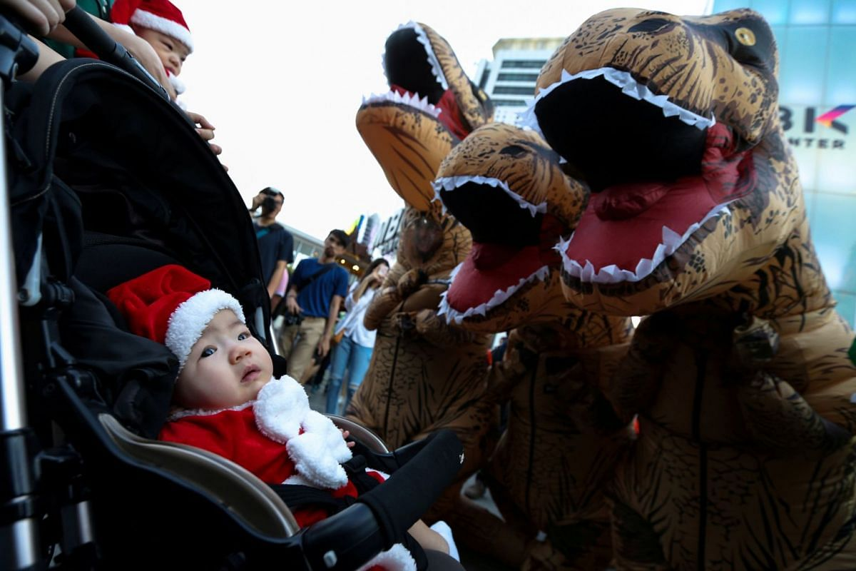 Performers wearing T-Rex costumes play with infants wearing Santa Claus costumes at a shopping district in Bangkok, Thailand, on Dec 16, 2017. PHOTO: REUTERS