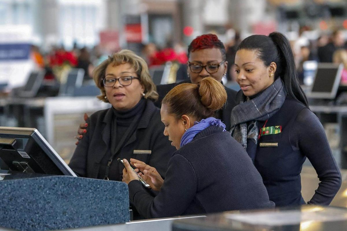 Airline agents look for answers on a mobile phone after a power outage at Hartsfield-Jackson Atlanta International Airport in Georgia, on Dec 17, 2017.