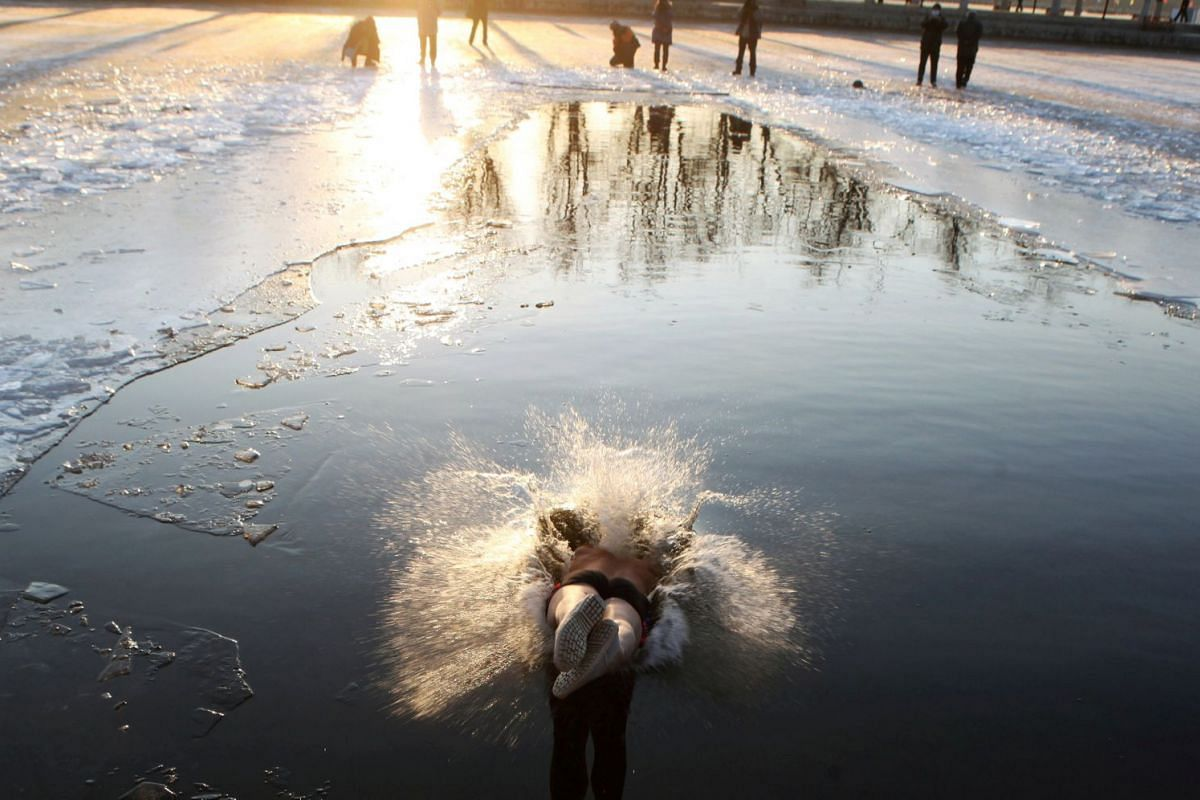 A winter swimmer dives into the icy waters of a river at a park in Shenyang, Liaoning province, China on Dec 18, 2017. PHOTO: REUTERS