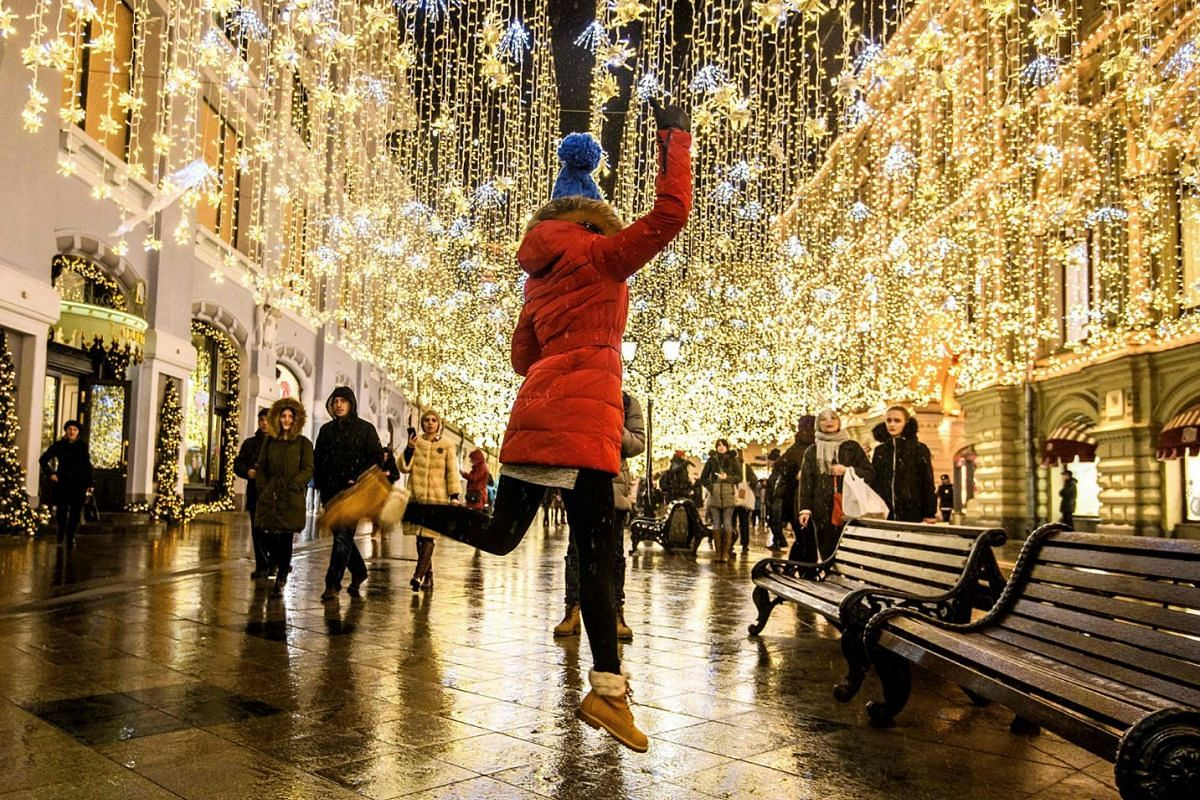 A girl jumps for a photo under the Christmas decorations set on a street in central Moscow on Dec 18, 2017. PHOTO: AFP