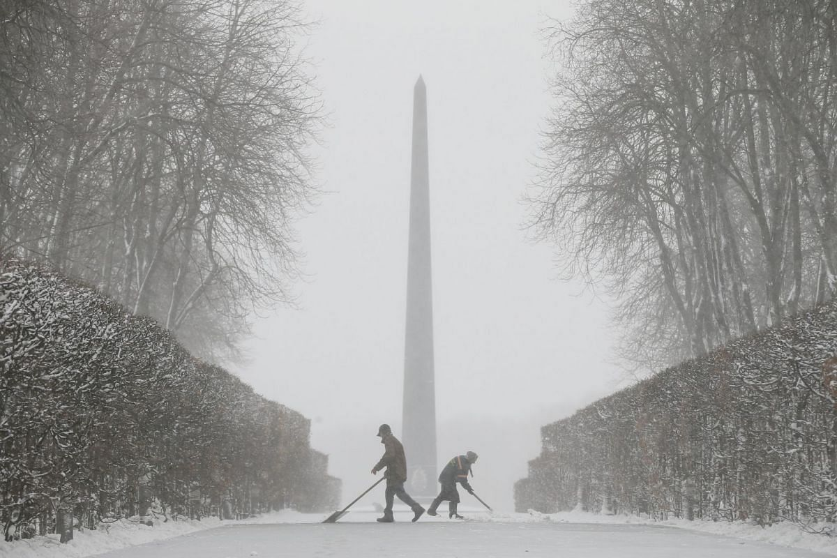 Workers remove snow during a heavy snowfall in Kiev, Ukraine on Dec 18, 2017.