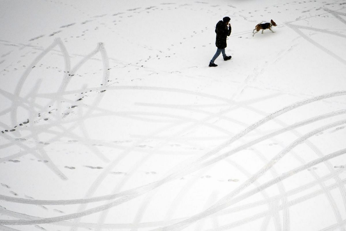 Footprints are seen on the snow as a pedestrian walks on a street during a snowfall in Lausanne, Switzerland, on Dec 18, 2017.