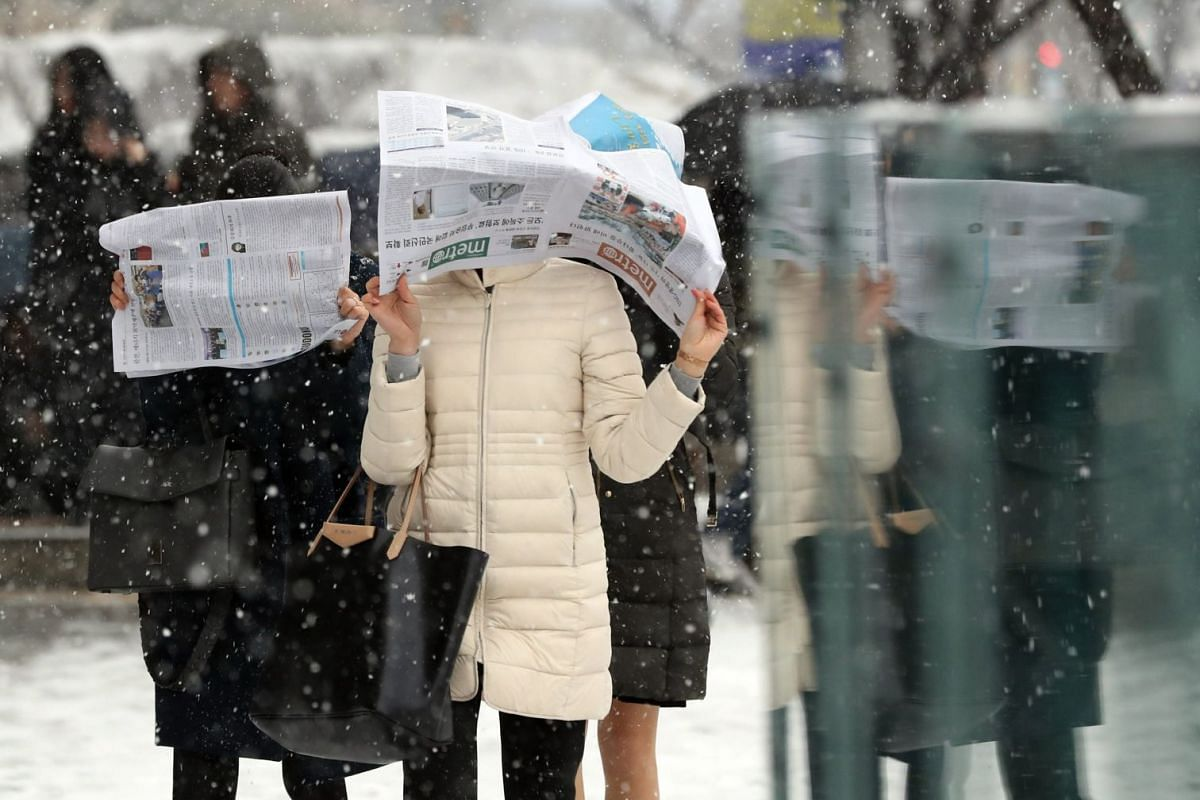 Pedestrians use newspapers to shield their heads from falling snow in downtown Seoul, South Korea, on Dec 18, 2017.