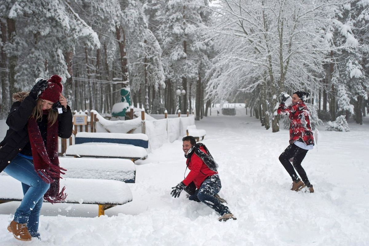 People play on a path covered by snow in Cabeza de Manzaneda mountain, in Galicia, Spain, on Dec 12, 2017.