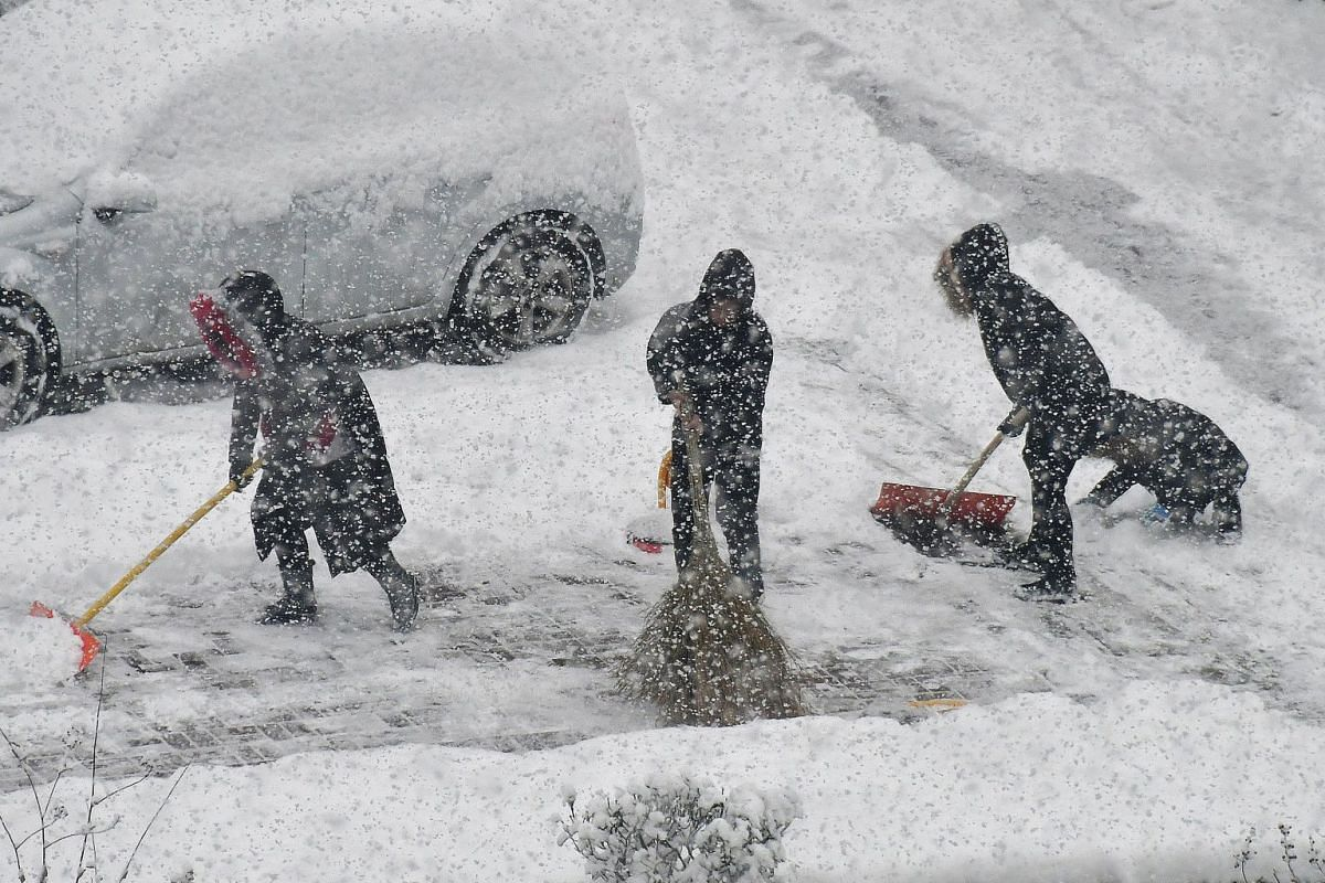 People clean up the road during snowfall in Yantai in China's eastern Shandong province on Dec 12, 2017.