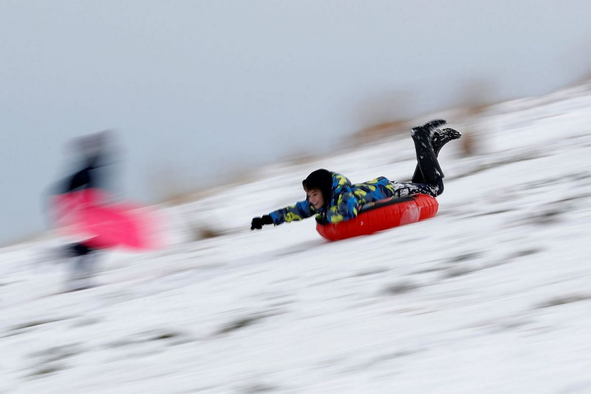 A boy slides on an inflatable tube in Bradgate Park after snow fall in Newtown Linford, Britain on Dec 11, 2017.