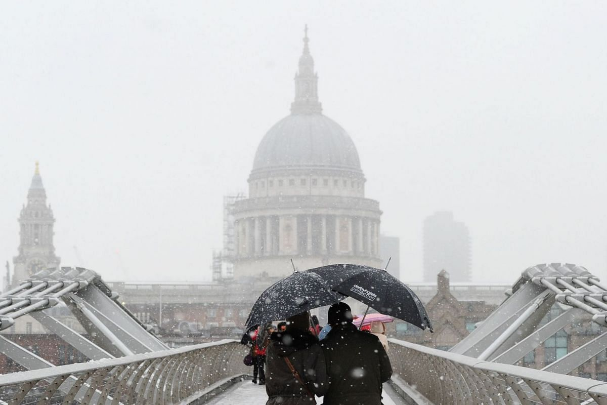 Pedestrians walk over the Millennium Bridge with St Paul's Cathedral pictured in the background as snow falls over central London on Dec 10, 2017.