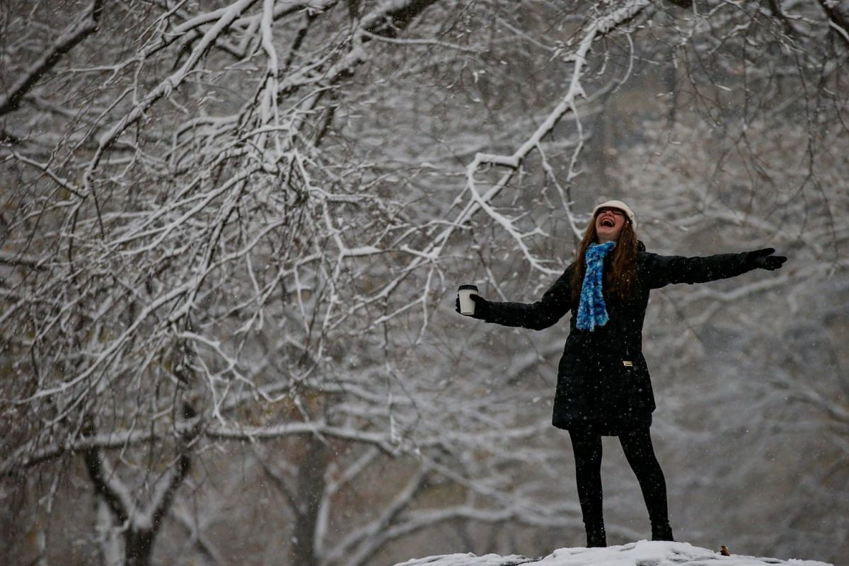 A woman reacts to the snow in Central Park during a pre-winter storm in New York, US, on Dec 9, 2017.