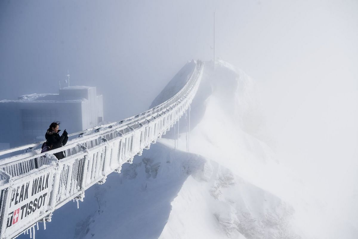 A tourist walks on the 'Peak Walk' suspension bridge on a winter day at the Glacier 3000 on the Col du Pillon between Gstaad and Les Diablerets, in Switzerland, December 20, 2017. PHOTO: EPA-EFE