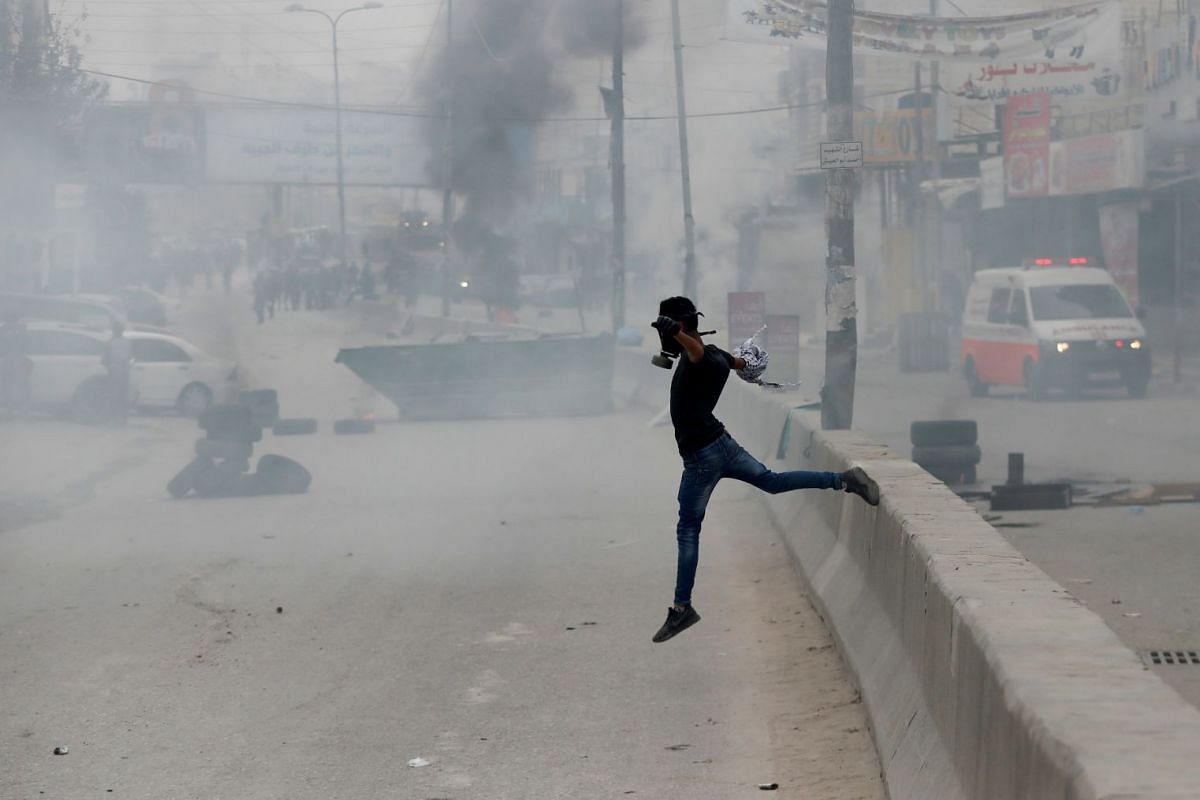 A protester jumps over a wall during a protest against U.S. President Donald Trump's decision to recognize Jerusalem as the capital of Israel, near Qalandia checkpoint near the West Bank city of Ramallah, December 20, 2017. PHOTO: REUTERS