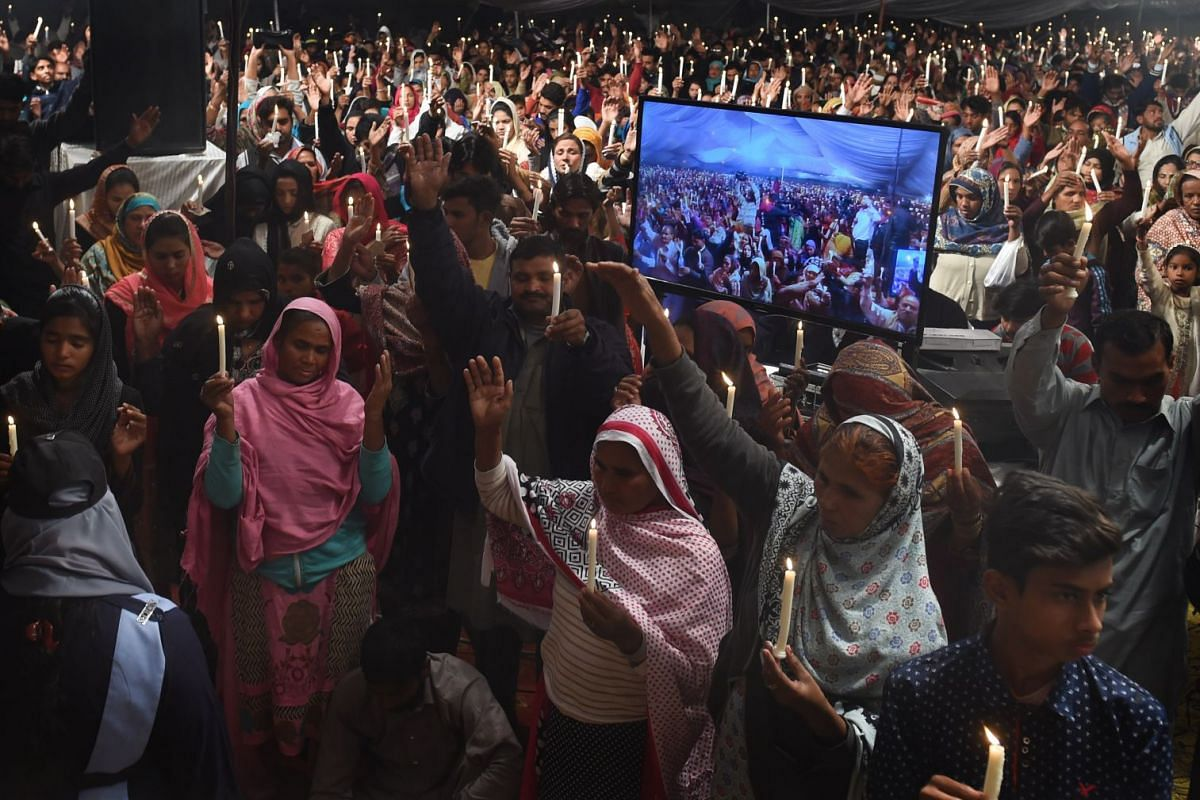 Pakistani well-wishers pray for the victims of a suicide attack on a church, in Lahore on December 20, 2017. PHOTO: AFP
