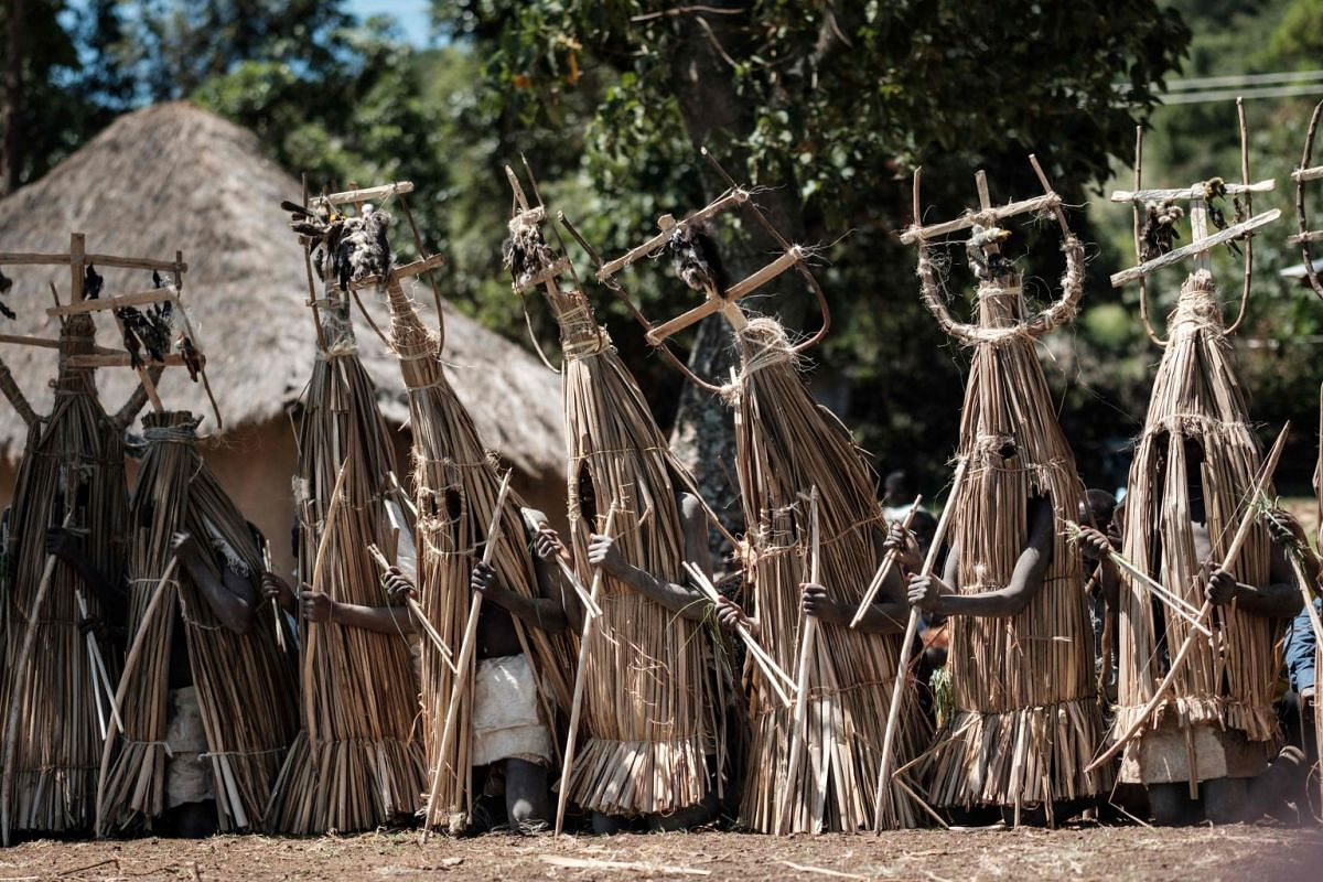 Circumcised Maasai young men wearing a ritual costume covered with hunted birds, come out from the bush to receive blessing from ceremony masters near Kilgoris, Kenya, on the last day of the annual one-month-long circumcision ceremony, on December 20