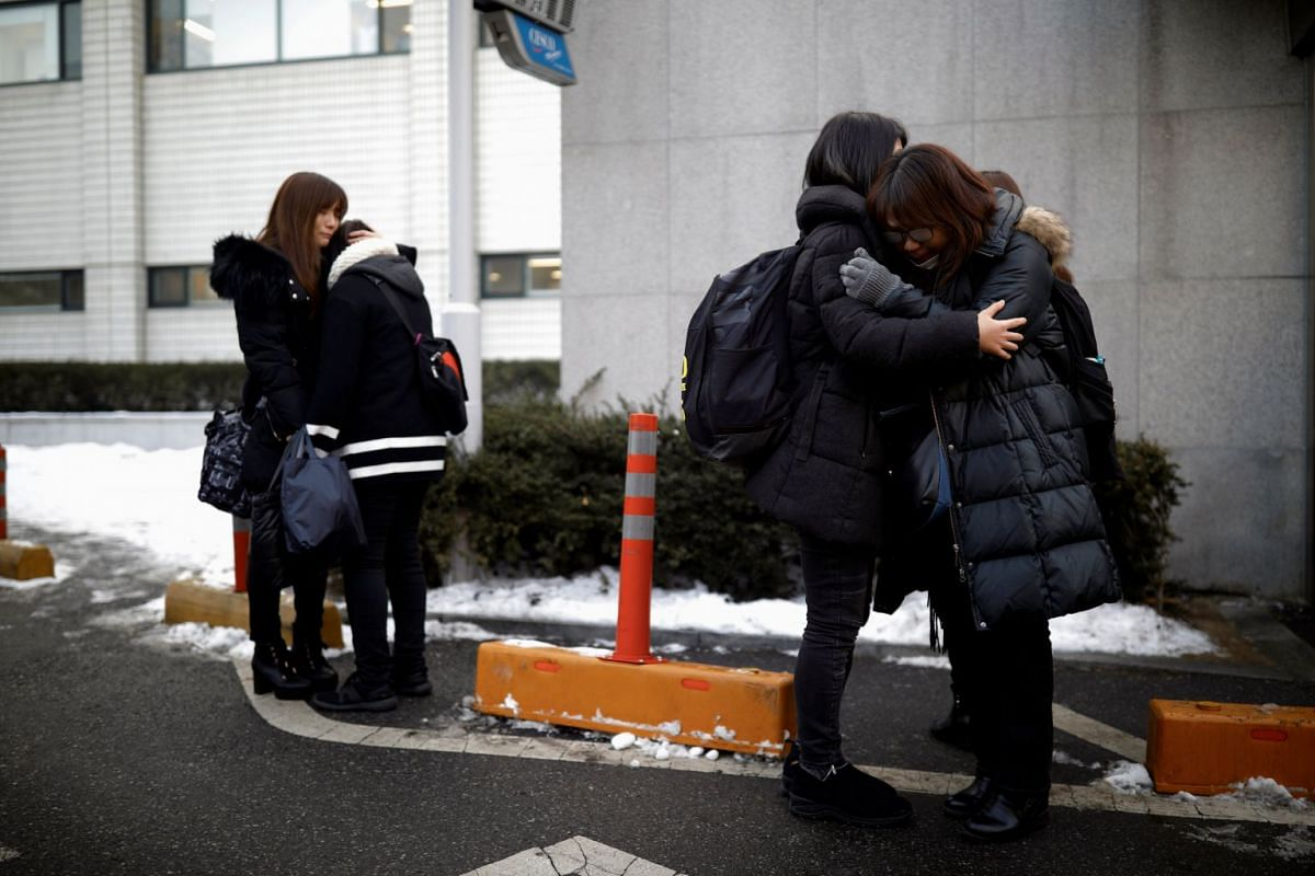 Fans of Kim Jong Hyun react as a hearse carrying his coffin leaves during his funeral at a hospital in Seoul on Dec 21, 2017.