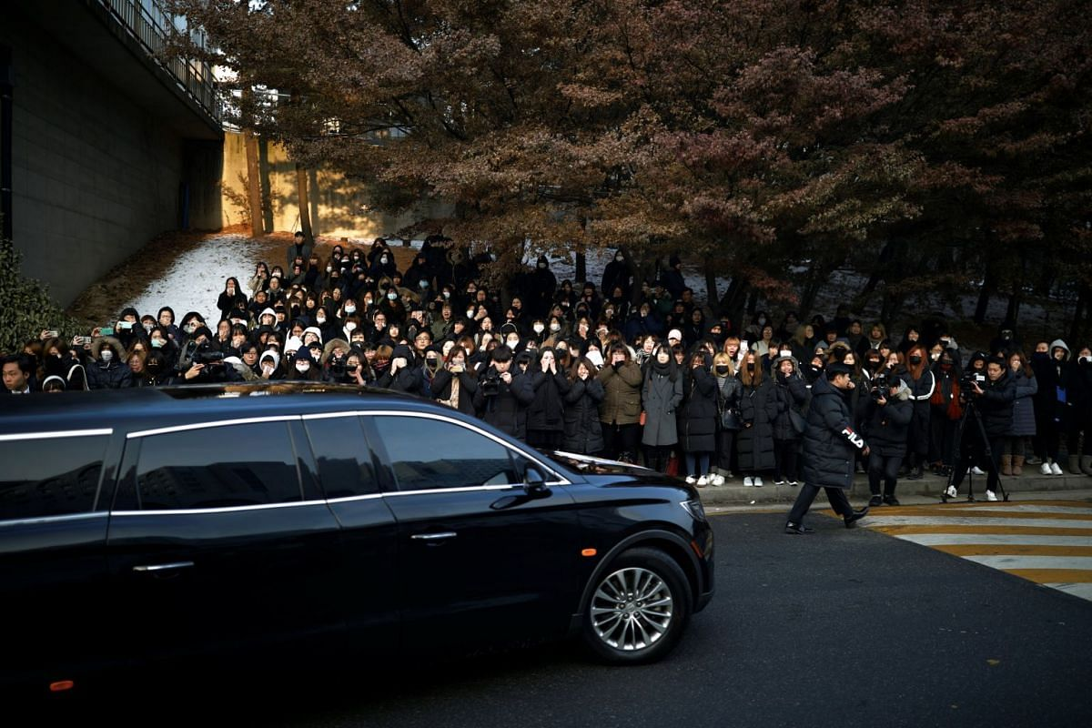 A hearse carrying the coffin of Kim Jong Hyun drives past his fans at a hospital in Seoul, South Korea, on Dec 21, 2017.