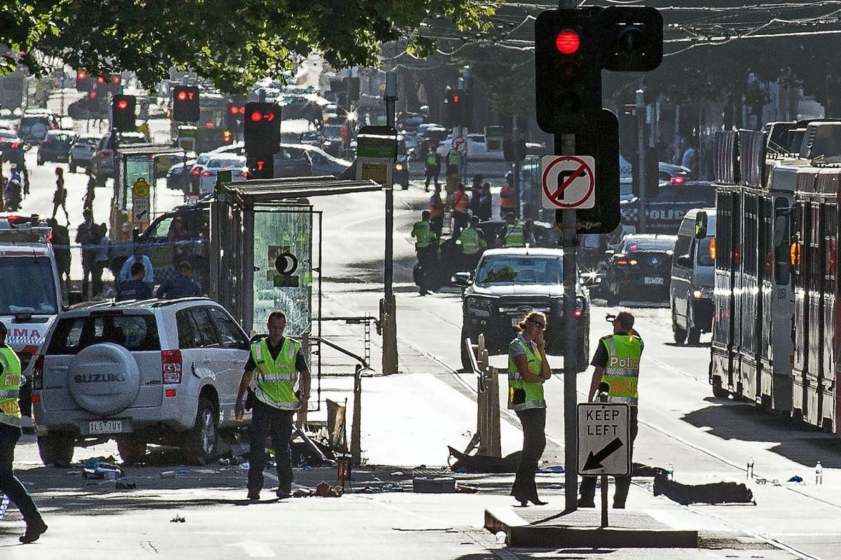 A white SUV (L) sits in the middle of the road as police and emergency personnel work at the scene of where a car ran over pedestrians in Flinders Street in Melbourne on December 21, 2017. The car ploughed into a crowd in Australia's second-largest c