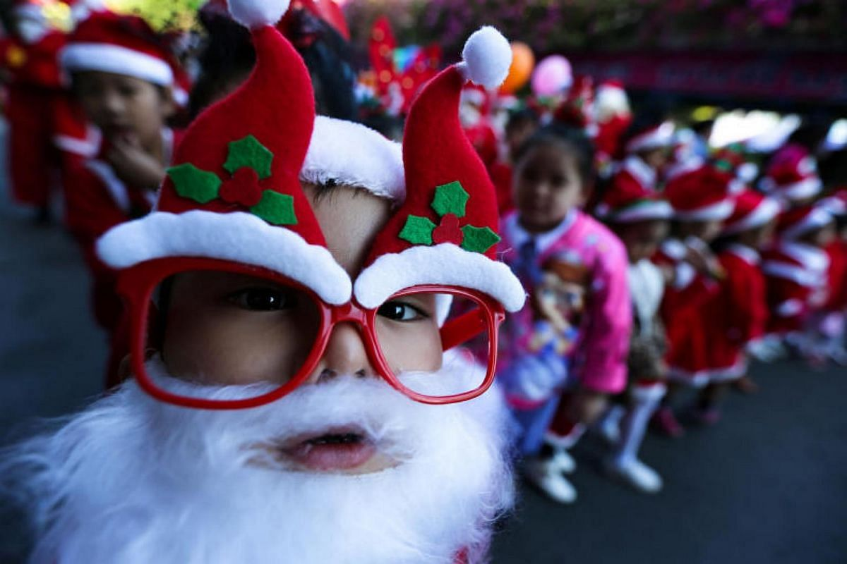 Students dressed in Santa Claus costumes take part during the Christmas celebrations at Jirasart school in Ayutthaya, Thailand, on Dec 22, 2017.