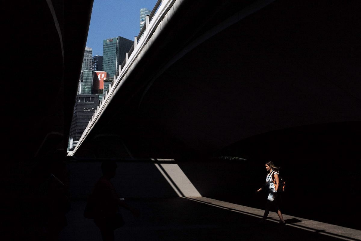 A woman walks across a streak of sunlight shining through an opening underneath the Esplanade bridge at 10.10am on June 20. The Central Business District is seen in the background. In a collaboration between The Straits Times and Leica, photojournali