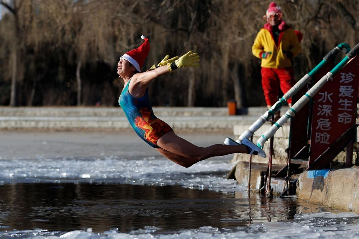 A woman wearing a Santa hat dives into a partly frozen lake in Shenyang in China's north-eastern Liaoning province.