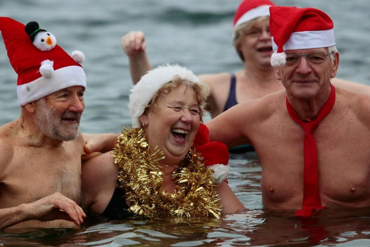 """Members of ice swimming club """"Berliner Seehunde"""" (Berlin Seals) take a dip in the Orankesee lake in Berlin as part of their traditional Christmas ice swimming session, in Berlin, Germany."""