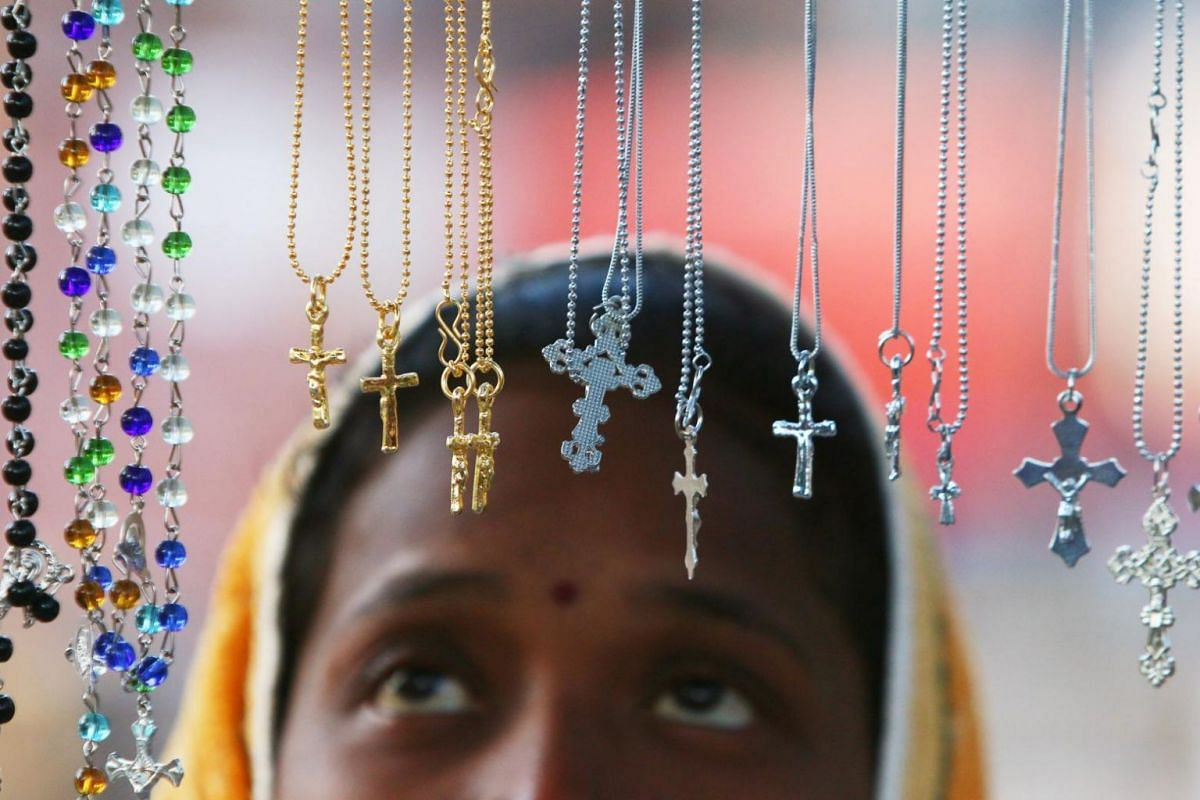 A woman looks at religious lockets at a stall outside a church during the Christmas celebrations in Chandigarh, India.
