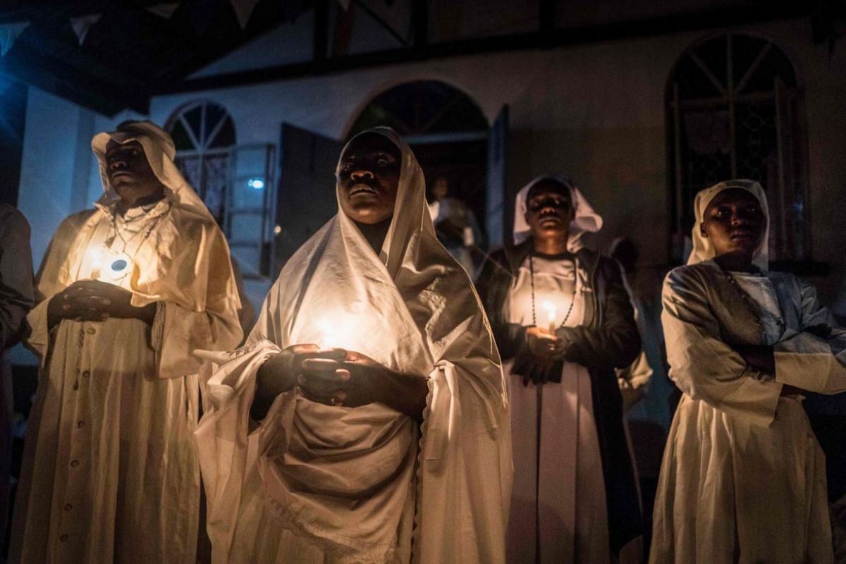 Believers of Legio Maria of African Church Mission hold candles during their overnight Christmas Mass at the church near Ugunja, Kenya.