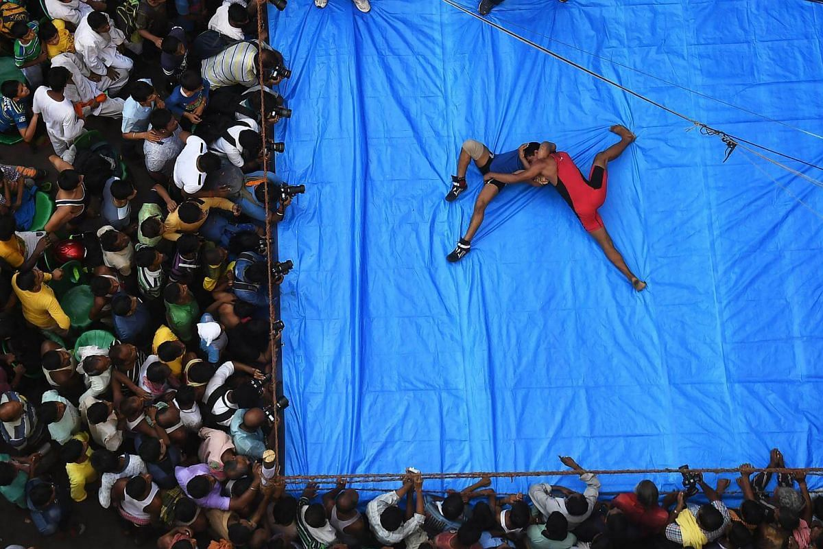 Indian amateur wrestlers participate in a friendly wrestling competition on a make-shift ring at the junction of a busy road organised as part of Diwali festivities in Kolkata on Oct 18, 2017.