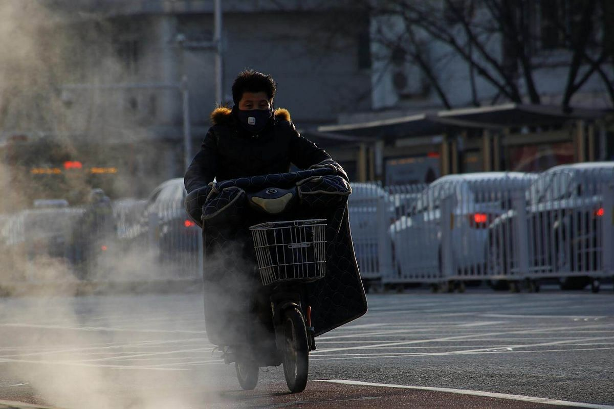 A man rides an electric scooter past steaming manhole covers on a cold day in Beijing, on Dec 1, 2017.