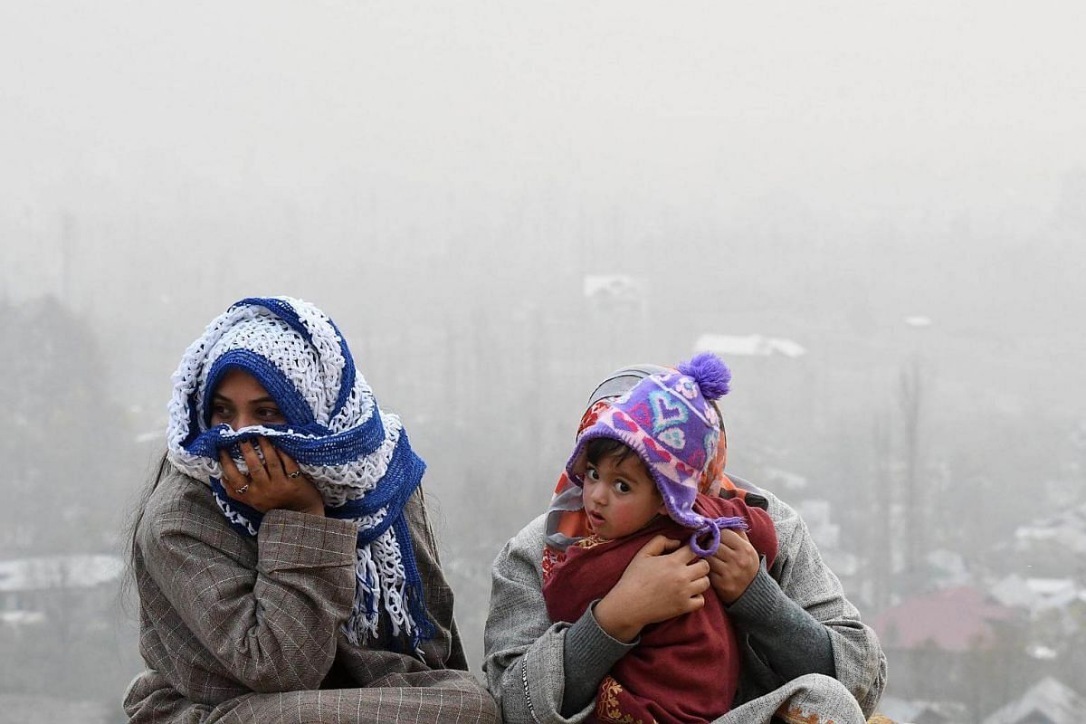 A Kashmiri muslim family sits on the top of the hill in the outskirts of Srinagar, on Nov 29, 2017.