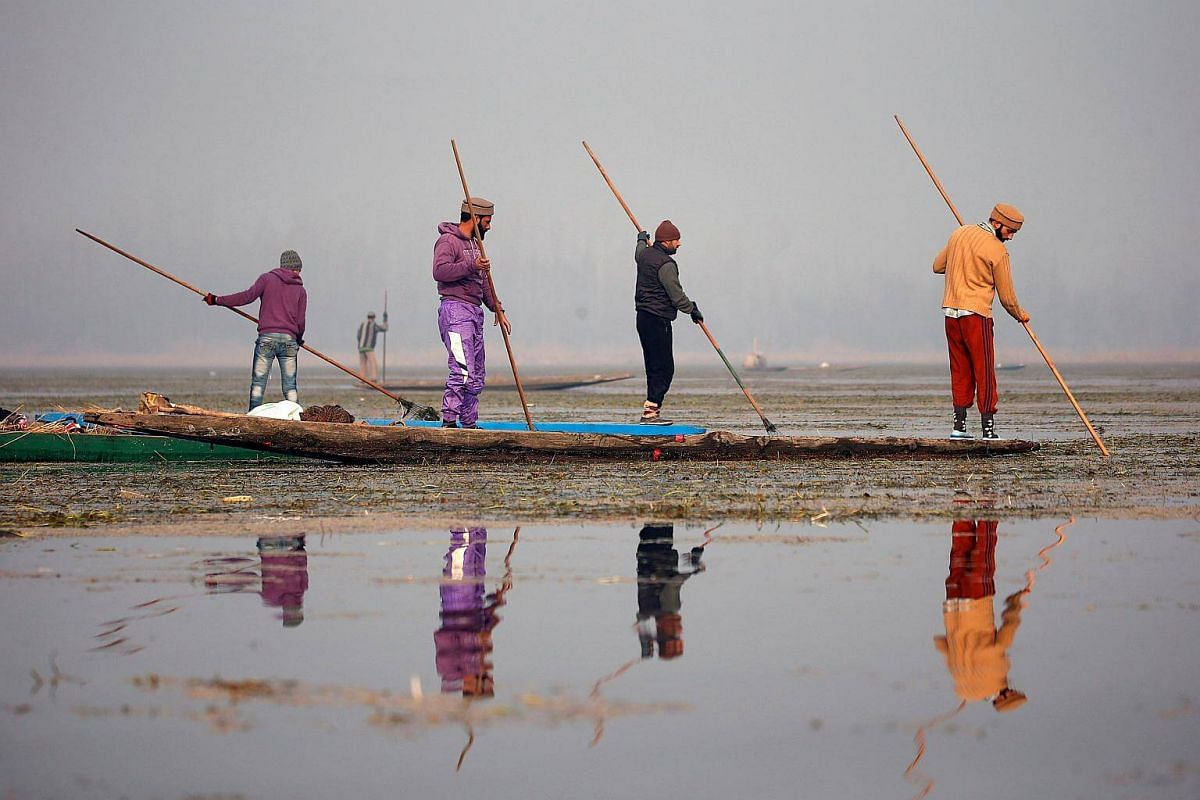 Fishermen use spears to catch fish in the waters of the Anchar Lake on a cold winter day in Srinagar, on Dec 28, 2017.