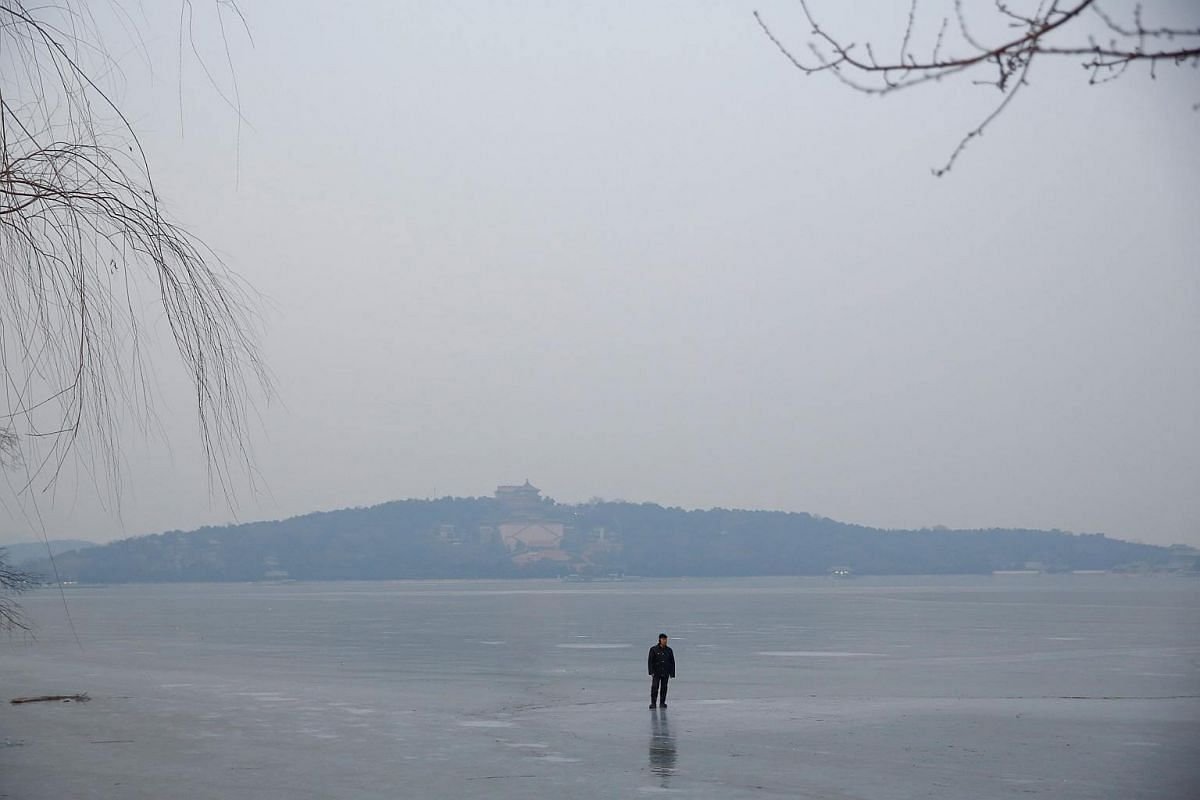 A worker stands on the frozen Kunming Lake at the Old Summer Palace in Beijing, on Dec 27, 2017.