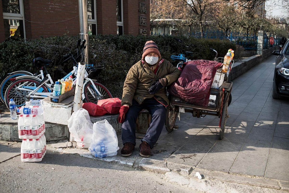 A man sells goods near the hospital on a cold day in Baoding, on Dec 13, 2017.