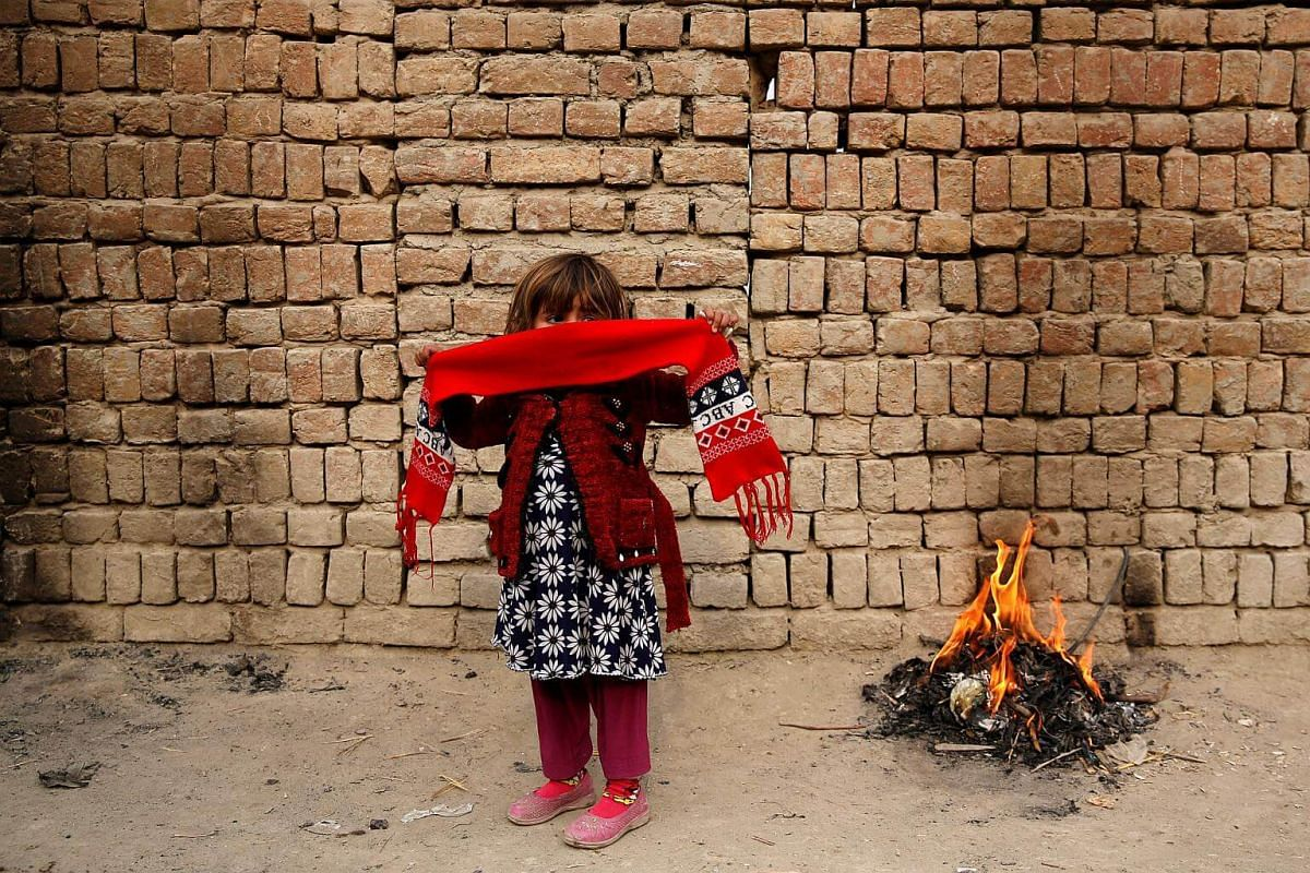 An Afghan girl stands next to fire on a cold winter morning in Kabul, Afghanistan, on Dec 11, 2017.