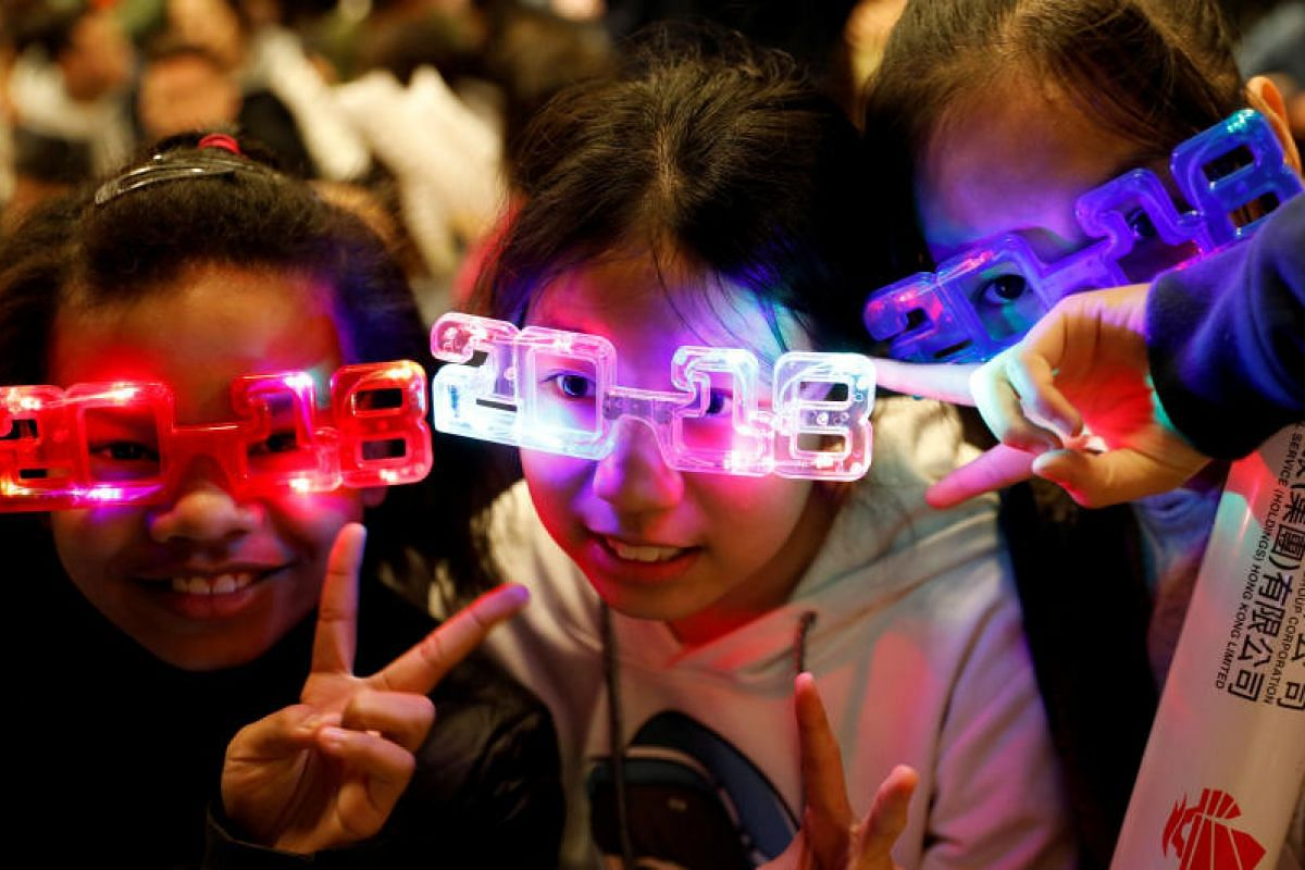 Children wear 2018 glasses as they wait for the new year fireworks in Hong Kong, China on Dec 31, 2017.