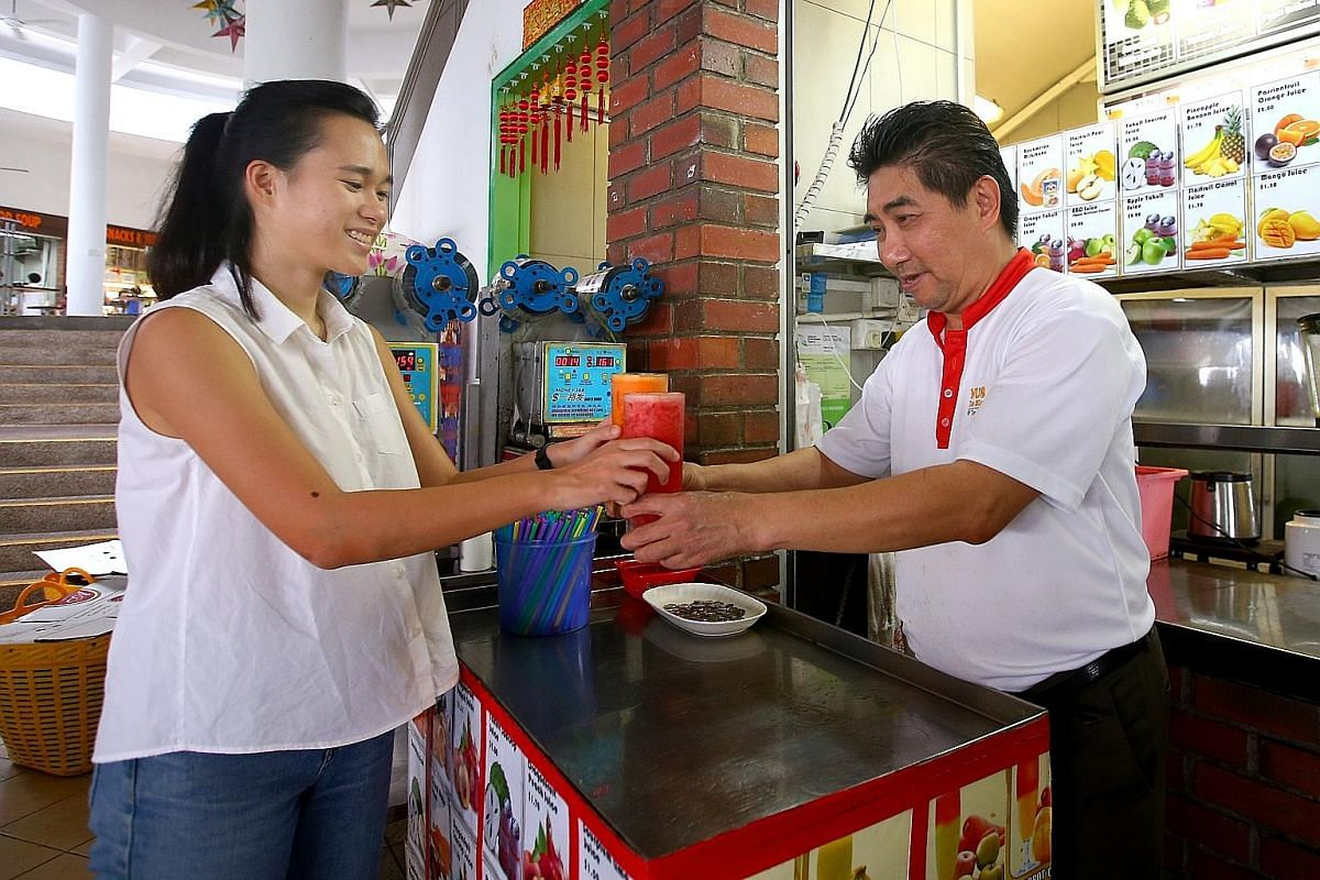 Ms Pamela Low gets her drink orders in reusable cups and without straws from Mr Henry Chua Kay Chee, who runs Fresh Fruit and Juices stall at the National University of Singapore.