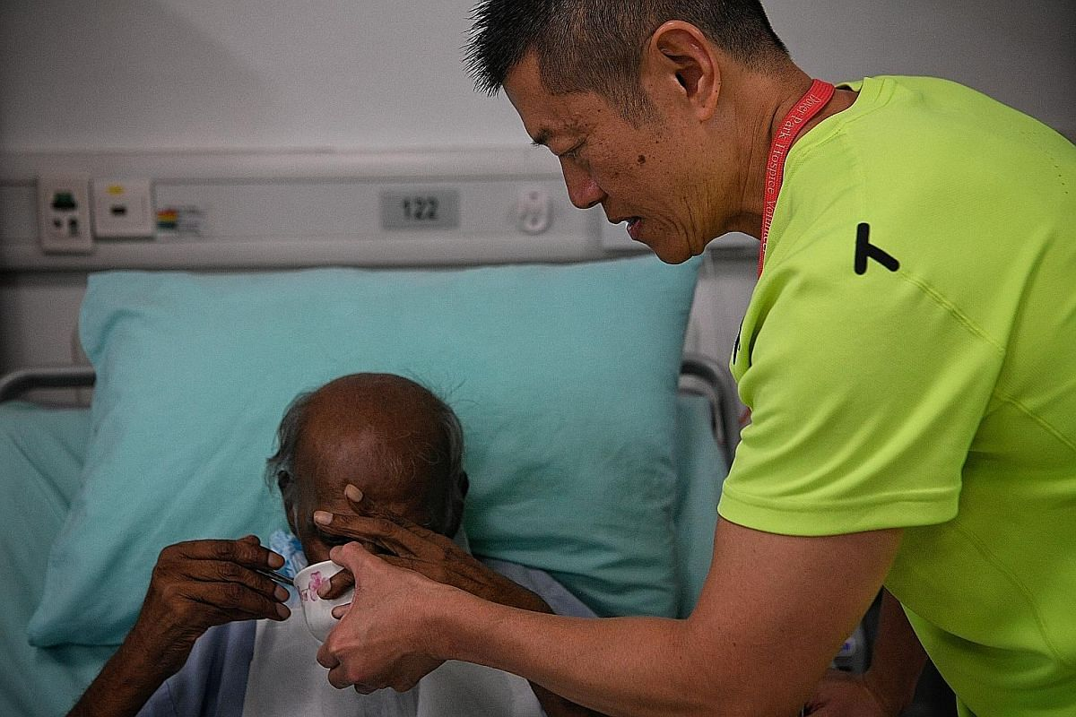 Customer service officer Gary Tee, 50, a volunteer with 20 years of service, helps feed a patient during a befriending session. Befrienders provide companionship and a listening ear to patients, and also to caregivers and family members. They also help pa