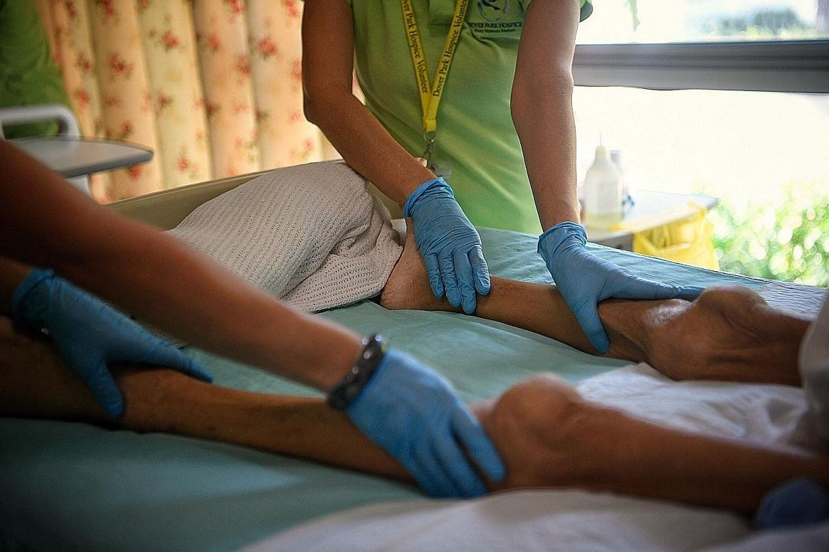 Full-time volunteer Mabel Pek (centre), 61, with 44-year-old teacher Chow Wai Mun, massages a resident's legs during a weekly massage-therapy session. Ms Pek heads a team of around 10 volunteers, and has trained over 100 in the art of Swedish massage. It