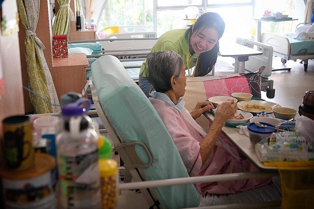 Ms Mikaela Low, an 18-year-old volunteer, speaks to a Dover Park Hospice resident during a befriending session. Ms Low started at the hospice helping out with administration, before training to be a befriender when she was 16. She also plays the piano in