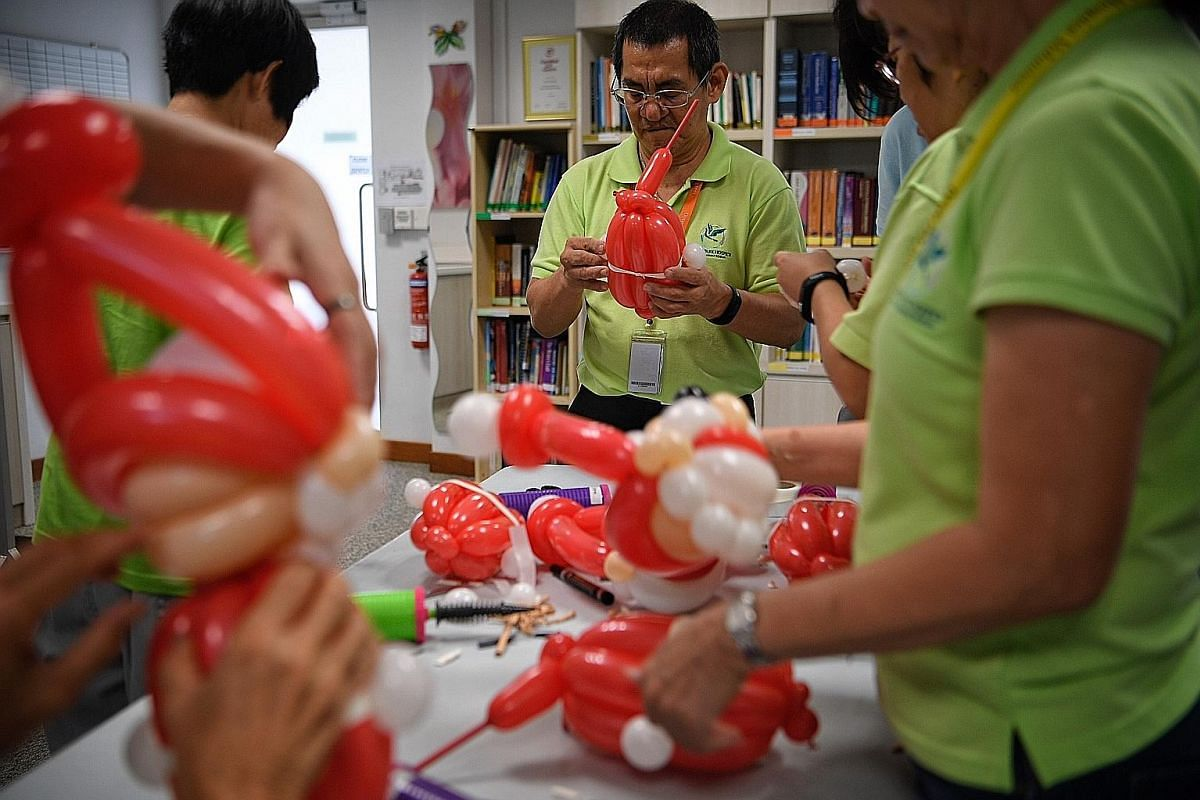 Mr Johnny Oh, a 59-year-old electrical maintenance officer and volunteer of 11 years, learns to sculpt balloons during a workshop at Dover Park Hospice. Under its Continuous Volunteer Education programme, Dover Park organises classes regularly to teach ne
