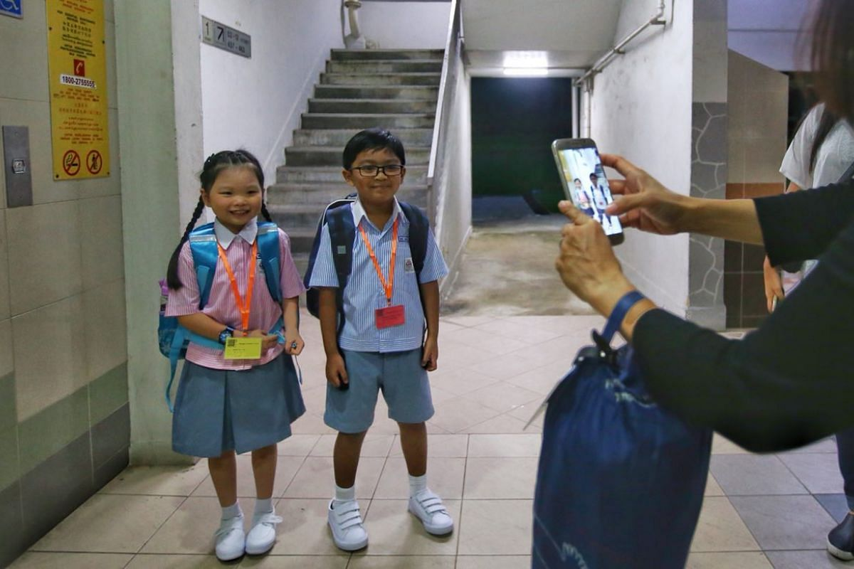 Six-year-old Grace Tng, and her neighbour Muhammad Aiman Aqmal Nor Md, also six, heading to Shuqun Primary School for their first day of primary school, Jan 2, 2018. PHOTO: THE STRAITS TIMES/GAVIN FOO