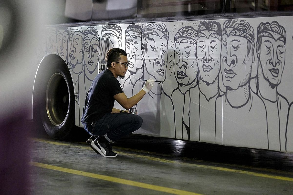Farizwan Fajari painting an SBS bus for the ArtScience Museum's upcoming exhibition of street art, where his work will be shown.