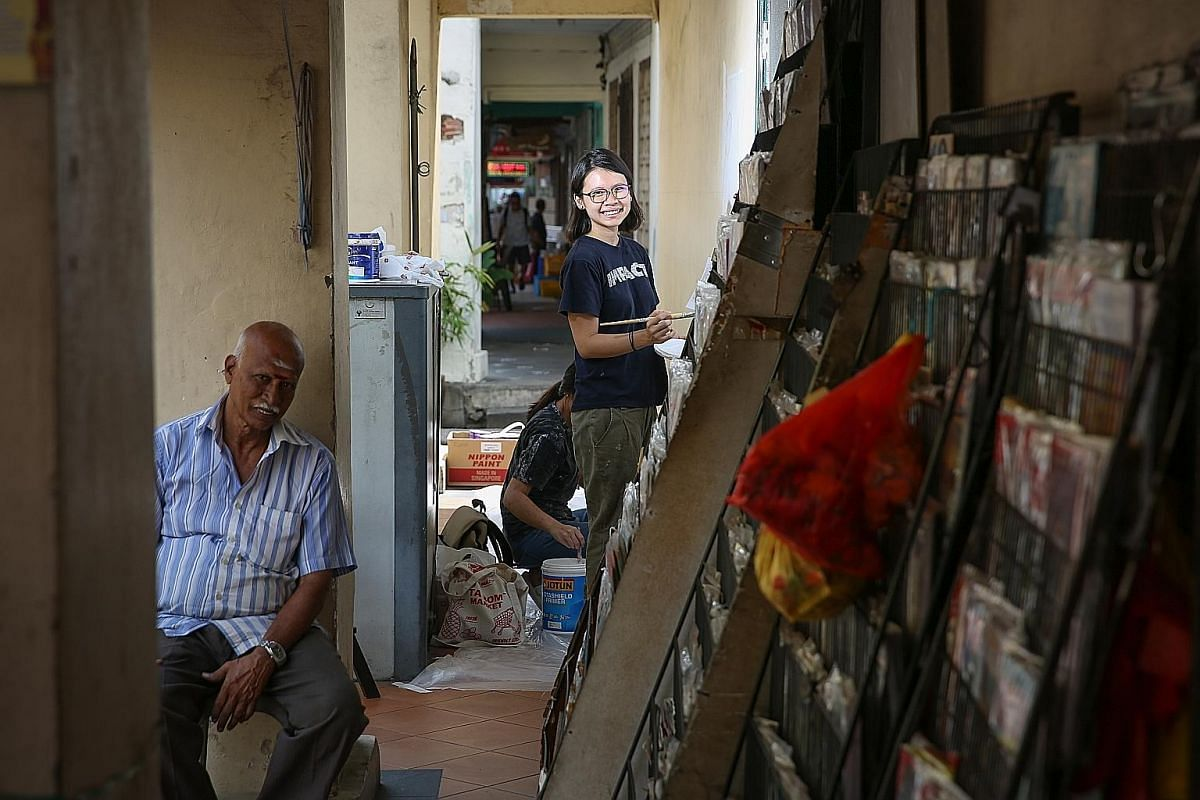 Artist Eunice Lim (centre) is painting a mural of a bookstore in Little India next to one owned by Mr M. Govindasamy (left), who has operated there for about 40 years.