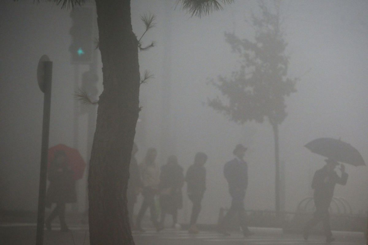 People cross the road on a pedestrian crossing during a foggy day in Jerusalem January 2, 2018. PHOTO: REUTERS