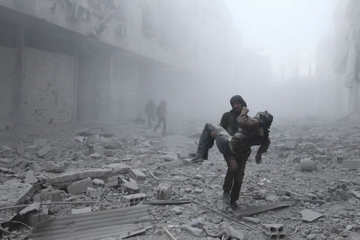 A wounded man is carried following an air strike on the rebel-held besieged town of Arbin, in the eastern Ghouta region on the outskirts of the capital Damascus on January 2, 2018. PHOTO: AFP