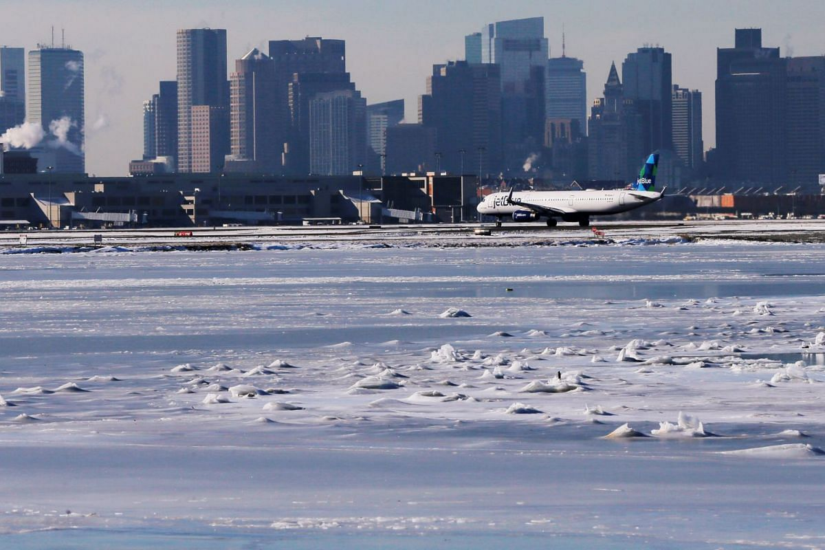 Ahead of an incoming winter snow storm, a JetBlue flight waits to take off from Logan International Airport next to the frozen waters of the Atlantic Ocean harbour between Winthrop and Boston, Massachusetts on Jan 3, 2018.