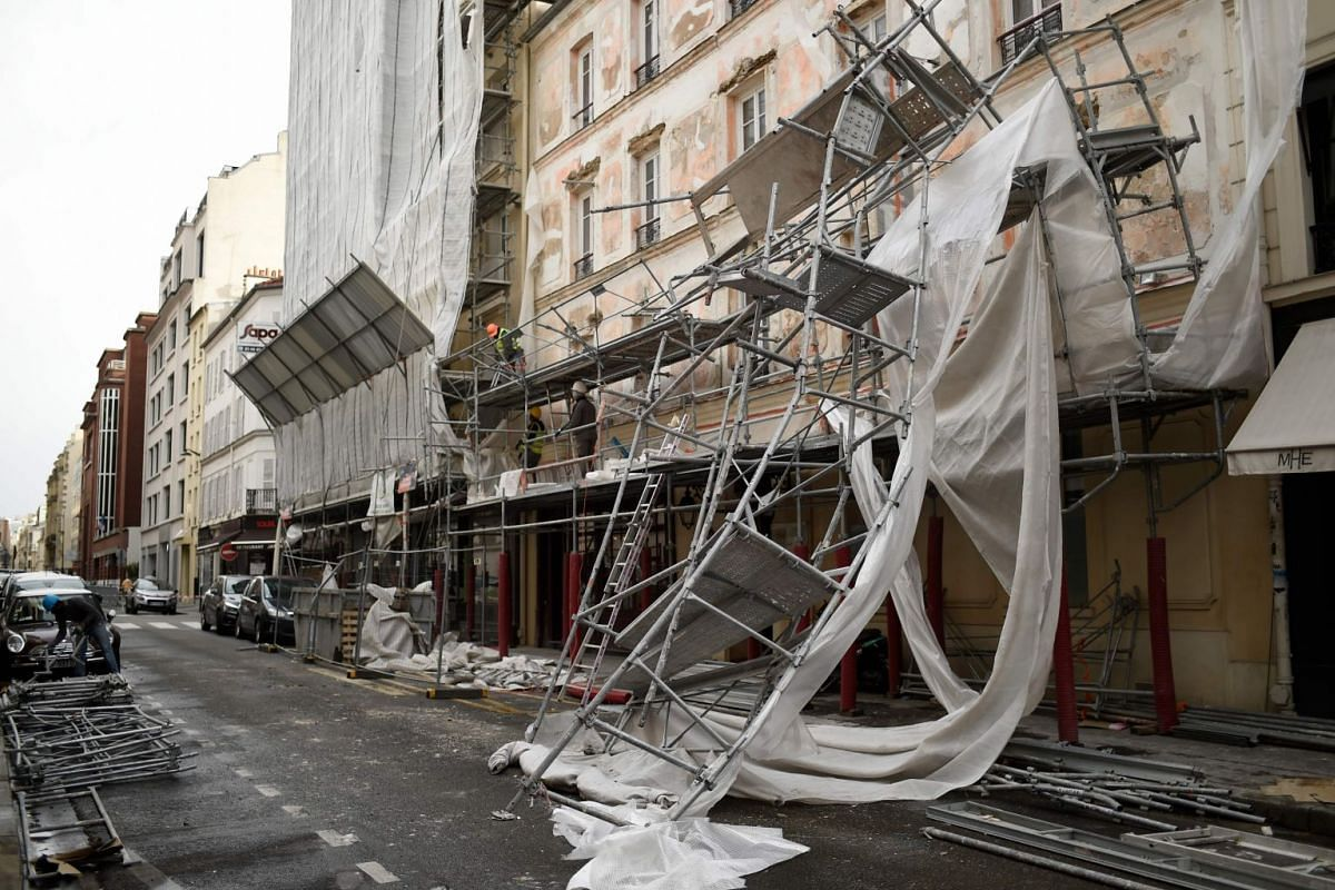 Workers assess damages after building scaffoldings collapsed due to strong winds in Paris' 17th district on Jan 3, 2018.