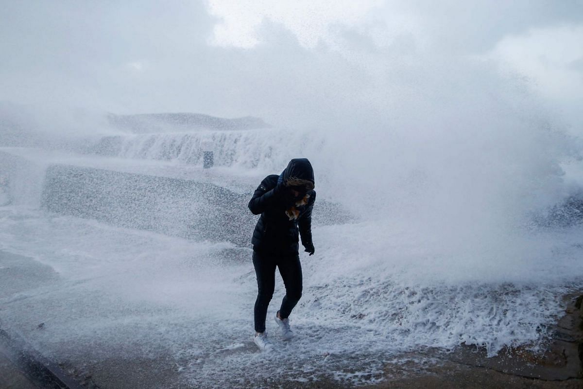 A woman takes cover from waves crashing against the seafront in Auderville, Normandy, as storm Eleanor hits the northern part of France on Jan 3, 2018.