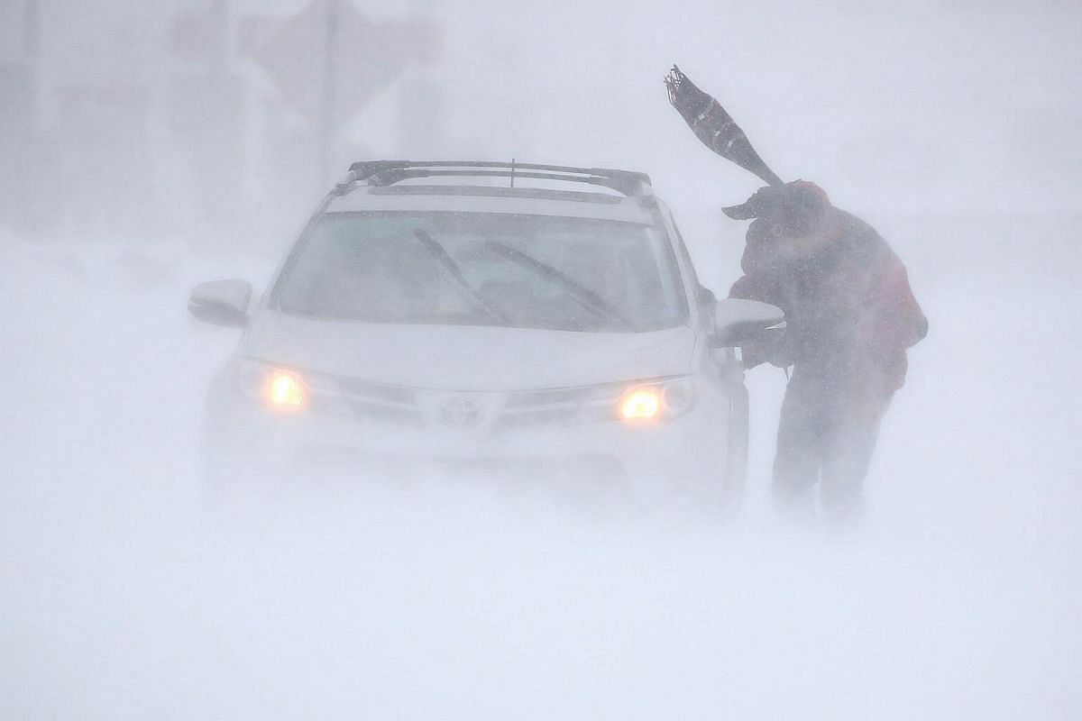 A man tries to get his car unstuck in near white out conditions as a storm passes in Rehoboth Beach, Delaware, on Jan 4, 2018.