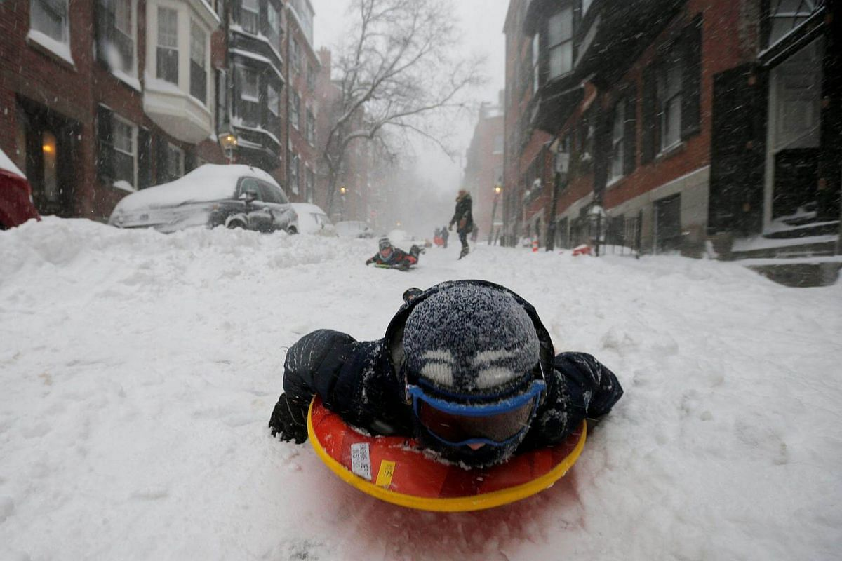 A boy sleds down a Beacon Hill street during Storm Grayson in Boston, on Jan 4, 2018.