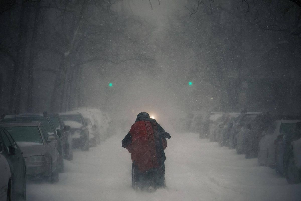A woman pushes a wheelchair laden with her belongings along an unplowed West 71st Street in New York, on Jan 4, 2018.